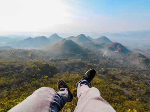 closeup photo of person s foot near mountain