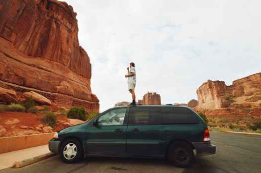 man standing on green mini van