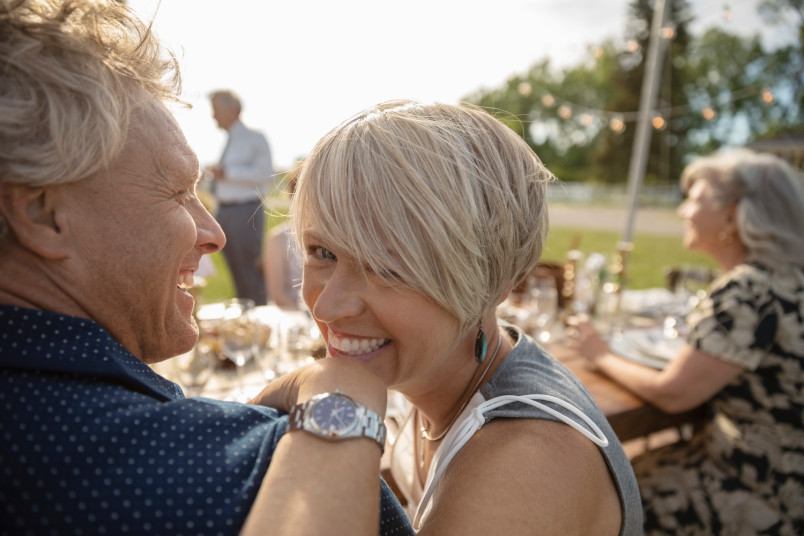 Portrait happy couple enjoying wedding reception at sunny patio table